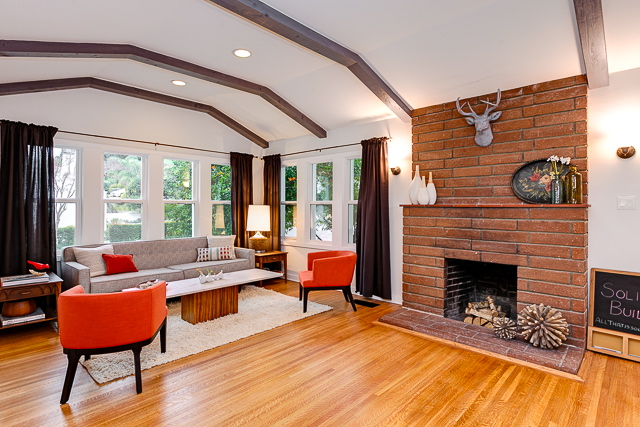 Living room with original wood floors, beamed/barreled ceiling and brick fireplace
