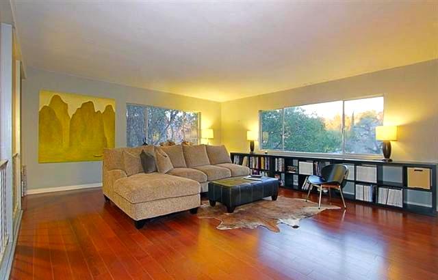 Living room with hardwood floors and treetop views