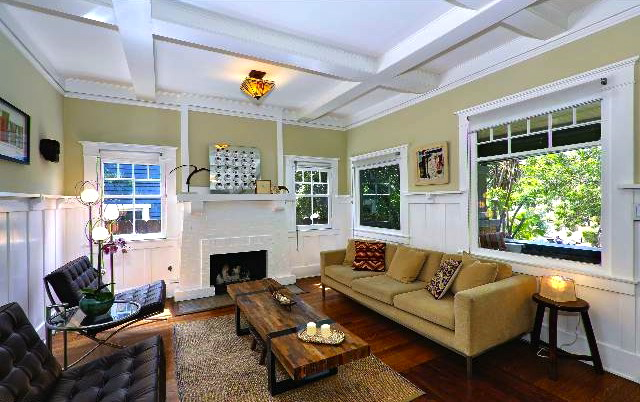 Living room with inlaid wood floors, coffered ceiling, wood windows and fireplace
