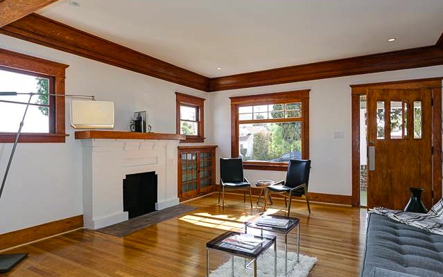Living room with original wood floors, moldings, fireplace and bulit-in