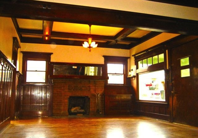 Living room with original wood floors, coffered ceilings, fireplace and windows