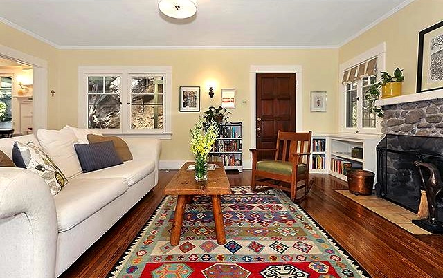 Living room with original wood floors, fireplace and windows