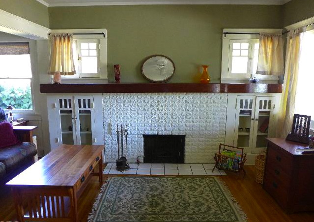 Living room with original fireplace, casement windows and wood floors