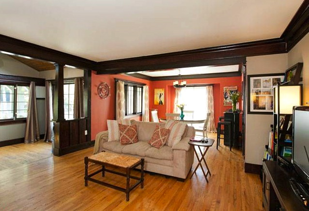 Living room with original wood floors, moldings and fireplace