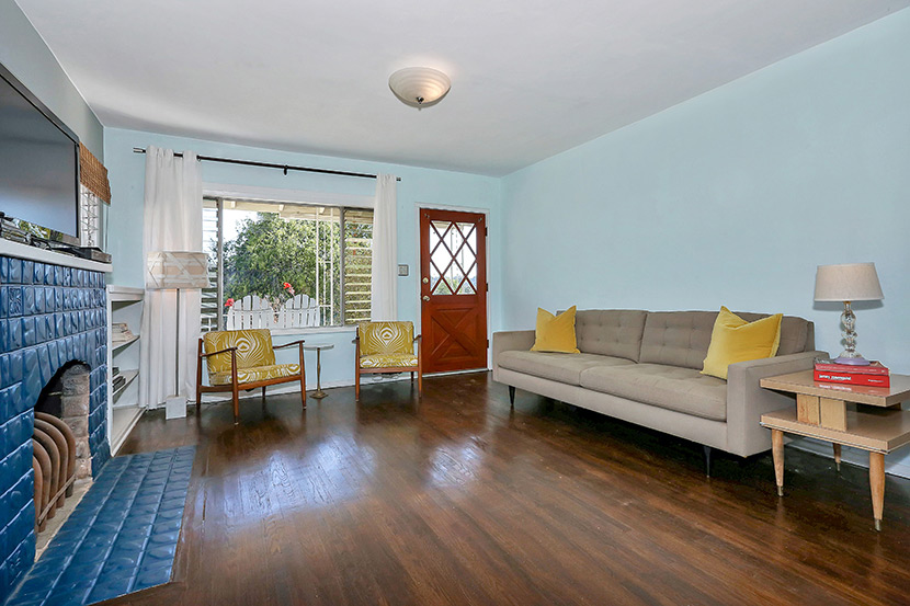 Living room with original wood floors, fireplace and jalousie windows