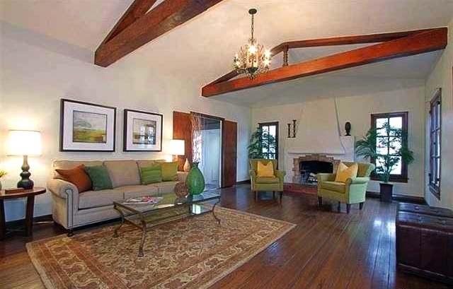 Living room with beamed/vaulted ceilings, wood floors and Batchelder fireplace