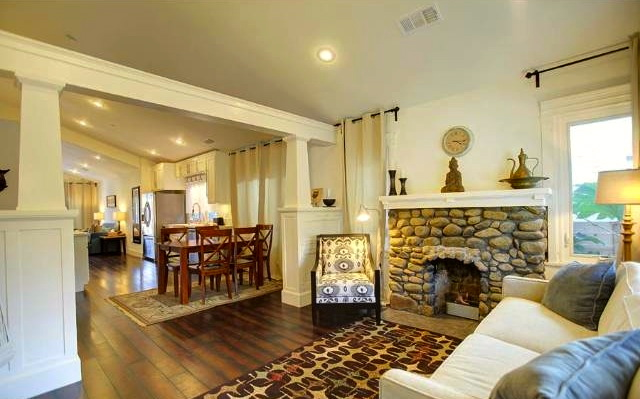 Living room with vaulted ceiling and river rock fireplace