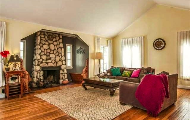 Living room with vaulted ceiling, wood floors and fireplace