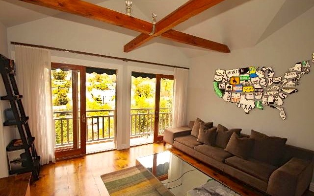 Living room with deck and beamed ceiling