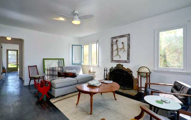 Living room with fireplace, wood floors and restored windows