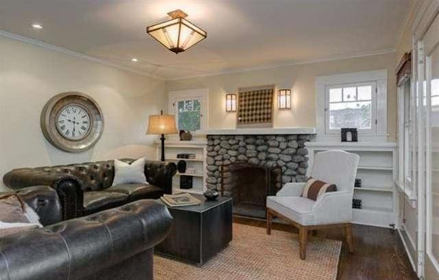 Living room with river rock fireplace and original wood floors