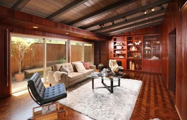 Den with built-ins and herringbone wood floors