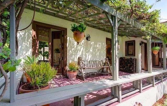 Pergola-flanked porch with mature vines. Courtesy of Scott Stephens – Keller Williams