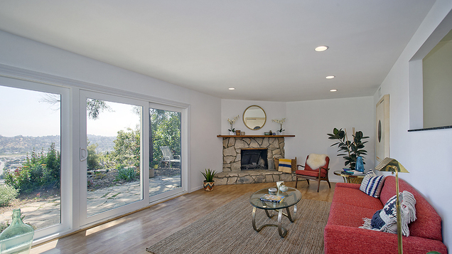 Living room with wood floors, fireplace and views