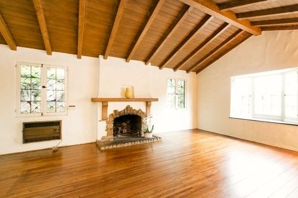 Living room with original wood floors, vaulted ceiling and fireplace